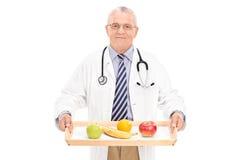 Reifer Doktor, der Behälter mit einigen Früchten auf ihm hält Lizenzfreie Stockbilder