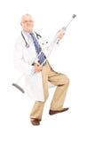 Reifer Doktor, der Gitarre auf einer Krücke spielt Stockfotografie