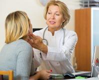 Reifer Doktor, der Lymphknoten des weiblichen Patienten überprüft Stockbilder