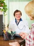 Reifer Doktor, der weiblichen Patienten konsultiert Lizenzfreies Stockfoto