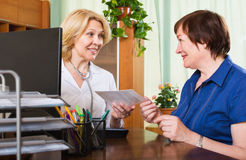 Reifer Doktor, der weiblichen Patienten konsultiert Stockbilder