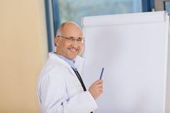 Reifer Doktor Standing Near Flipchart in der Klinik Lizenzfreie Stockfotografie
