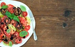 Reifer Dorferbstück-Tomatensalat mit Olivenöl und Basilikum über rustikalem hölzernem Hintergrund, Draufsicht Lizenzfreie Stockbilder