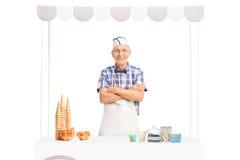 Reifer Eiscremeverkäufer, der hinter einem Kiosk steht stockfotos
