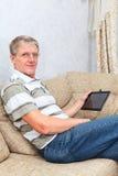Reifer erwachsener Mann, der mit einer neuen Tabletteeinheit arbeitet Stockbild