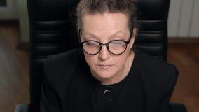 Reifer Frau Brunette in den Gläsern arbeitet an dem Computer, der im Stuhl sitzt stock footage