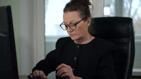 Reifer Frau Brunette in den Gläsern und im schwarzen Anzug schreibend auf Computer im Büro, das vor Fenster sitzt stock footage