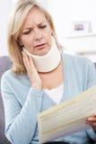 Reifer Frauen-Lesebuchstabe, nachdem Nackenverletzung empfangen worden ist stockfoto