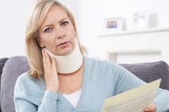 Reifer Frauen-Lesebuchstabe, nachdem Nackenverletzung empfangen worden ist stockbilder