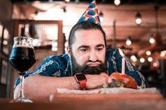 Reifer Geburtstagsmann, der keinen Appetit betrachtet sein Lebensmittel hat stockbilder