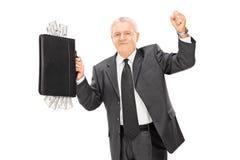 Reifer Geschäftsmann, der Aktenkoffer voll vom Bargeld hält Lizenzfreie Stockfotografie