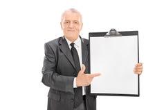 Reifer Geschäftsmann, der auf ein Klemmbrett zeigt Lizenzfreies Stockfoto