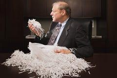 Reifer Geschäftsmann, der mit Papier-shreddings spielt Lizenzfreie Stockfotos