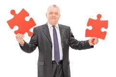 Reifer Geschäftsmann, der zwei Stücke eines Puzzlespiels hält Stockfoto