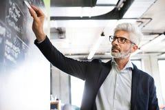 Reifer Geschäftsmann mit dem grauen Haar im Büro Stockbilder