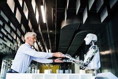 Reifer Geschäftsmann oder ein Wissenschaftler mit Roboter Stockfotos