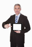 Reifer Geschäftsmann Showing Digital Tablet Lizenzfreie Stockfotos