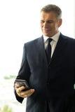 Reifer Geschäftsmann unter Verwendung des Smartphone Lizenzfreie Stockbilder