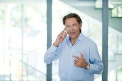 Reifer Geschäftsmann unter Verwendung seines Telefons im Büro - erfolgreicher Geschäftsmann - modernes Büro stockfoto