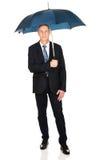 Reifer Geschäftsmann in voller Länge mit Regenschirm Lizenzfreie Stockbilder