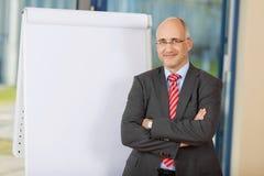 Reifer Geschäftsmann With Arms Crossed, das Flipchart bereitsteht Stockfoto