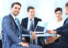 Reifer Geschäftsmann, der während der Sitzung mit Kollegen lächelt Stockfoto