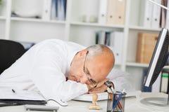Reifer Geschäftsmann Sleeping On Desk Stockbild