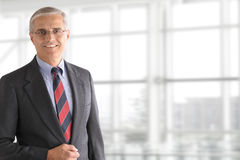 Reifer Geschäftsmann Standing im Büro Stockbild