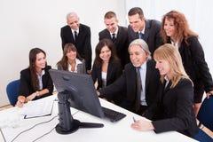 Reifer Geschäftsmann With Team Discussing Stockfoto