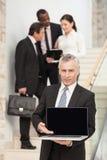 Reifer Geschäftsmann unter Verwendung des Laptops mit Führungskräften an der Rückseite Lizenzfreie Stockfotos