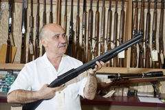 Reifer Gewehrgeschäftsinhaber, der Waffe im Shop betrachtet Stockbild