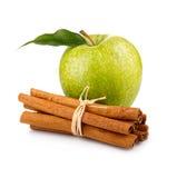 Reifer grüner Apfel mit den Zimtsteuerknüppeln getrennt Stockfotografie