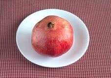 Reifer großer Granatapfel auf weißer Platte über roter karierter Tischdeckennahaufnahme Lizenzfreie Stockfotografie