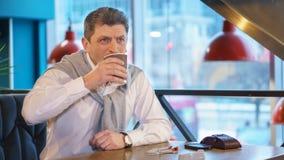 Reifer gutaussehender Mann in einem weißen Hemd mit Strickjacke trinkt den kürzlich gemachten Morgenkaffee Stockfotografie