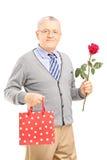 Reifer Herr, der eine Rosenblume und -tasche hält Lizenzfreies Stockfoto