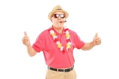 Reifer Herr, der eine Zigarre raucht und Daumen aufgibt Stockfoto