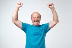 Reifer hispanischer Mann im blauen T-Shirt Sieg seines Teams über grauem Hintergrund feiernd lizenzfreies stockfoto
