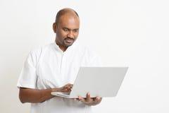 Reifer indischer Mann, der Laptop verwendet Stockbilder