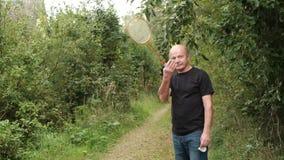 Reifer kaukasischer Mann, der das Badminton im Freien spielt stock footage