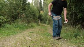 Reifer kaukasischer Mann, der das Badminton im Freien spielt stock video footage
