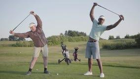 Reifer kaukasischer Mann und junger nahöstlicher Mann, der Golf auf dem Golffeld spielt Spieler, die vor dem Spiel aufwärmen stock footage