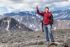 Reifer kaukasischer Wanderer, den ein Mann zur Gebirgsspitze darstellt, sprechend am Handy Lizenzfreie Stockbilder