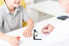 Reifer Kinderarzt, der Empfehlungen für kleinen Patienten macht lizenzfreie stockbilder