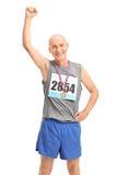 Reifer Läufer mit der Medaille, die seine Faust anhebt Stockfotografie