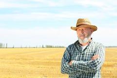 Reifer Landwirt, der auf dem Gebiet steht stockfotografie