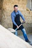 Reifer Landwirt mit großer Schaufel in der Scheune Lizenzfreies Stockfoto