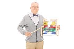 Reifer Lehrer, der mit einem Stock auf einem Abakus zeigt Stockbild
