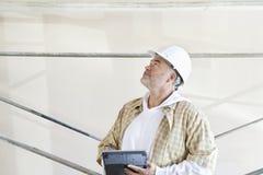 Reifer männlicher Architekt, der eine Anmerkung in der digitalen Tablette beim Baustelle oben betrachten macht lizenzfreies stockfoto