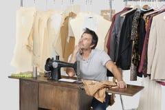 Reifer männlicher denkender Schneider beim Sitzen an Nähmaschine mit Gewebe stockfoto