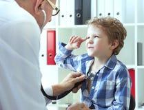 Reifer männlicher Doktor, der einen Kinderpatienten durch Stethoskop überprüft Stellen Sie schützende Schablone und die Pille geg Lizenzfreie Stockbilder